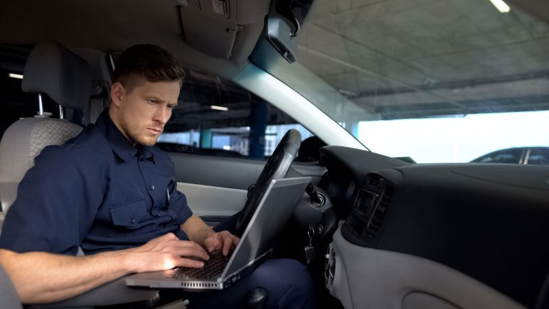 Male police officer working on laptop in car, filling data in crime report