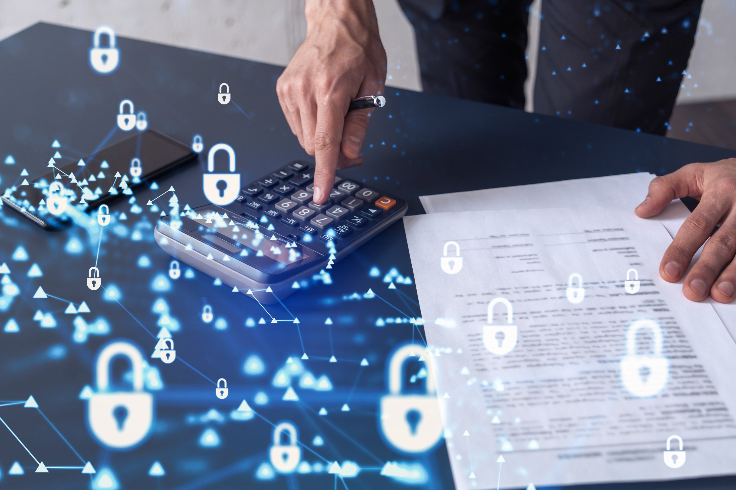 A businessman computing probability of risks in cyber security protection using calculator. Padlock Hologram icons over the working desk. Formal wear.