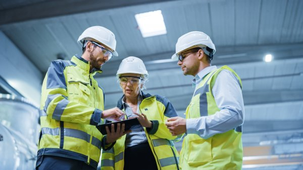 Three Heavy Industry Engineers Stand in Pipe Manufacturing Factory, Use Digital Tablet Computer, Have Discussion. Design and Construction of Large Oil, Gas and Fuels Transport Pipeline. Low Angle